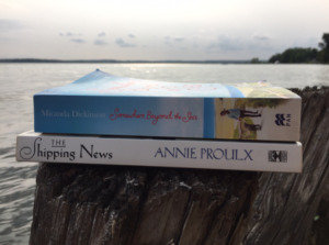 Spines of books The Shipping News by Annie Proulx and Somewhere Beyond the Sea by Miranda Dickinson, PCG Books, on driftwood posts overlooking Lake Simcoe.