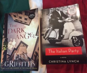 Books The Dark Angel by Elly Griffiths and The Italian Party by Christina Lynch laying face up on the colours of the Italian flag - green, white and red.