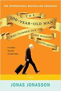 Yellow cover of an old man hunched out and pulling a suitcase behind him.
