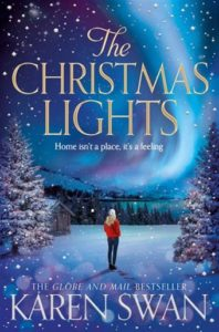 Northern lights brightens up a blue sky and blue-green water. Gold flakes of snow falls on the back of a woman in a red sweater surrounded by snow-covered pine trees.