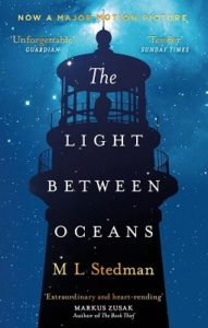 Silouette of a man standing in the top of a lighthouse srounded by a star-filled night.
