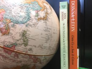 A globe that is focussed on Japan and two books - The Woman in the White Kimono and Unto Us a Son is Given