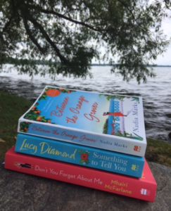 Three books sitting on a rock overlooking water and a tree.