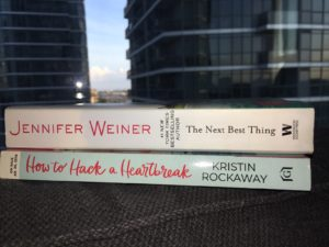 Spines of two books - The Next Best Thing and How to Hack a Heartbreak in front of condos