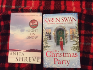 Two books Anita Shreve's Light on Snow and Karen Swan's The Christmas Party on a plaid red and black blanket