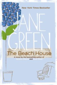 Blue front cover image of THe Beach House by Jane Green with an illustration of a blue flower and a chair and umbrella on the beach