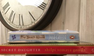 Spines of two books - The Beach House and The Secret Daughter, in front of a white-washed wall and a clock